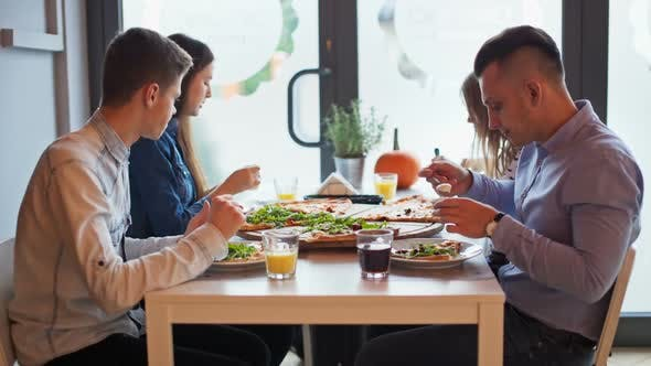 Four Young Friends Are Talking During a Meal with Big Pizza