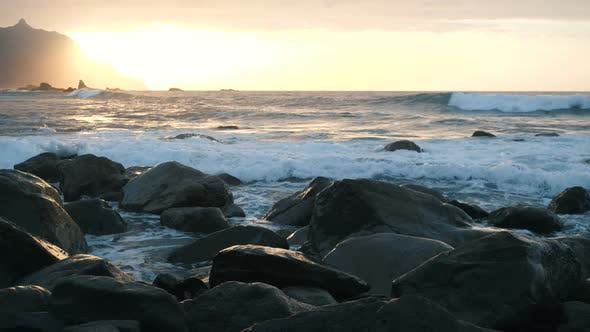 Ocean Waves Crash on Rocks and Spray in Beautiful Sunset Light at