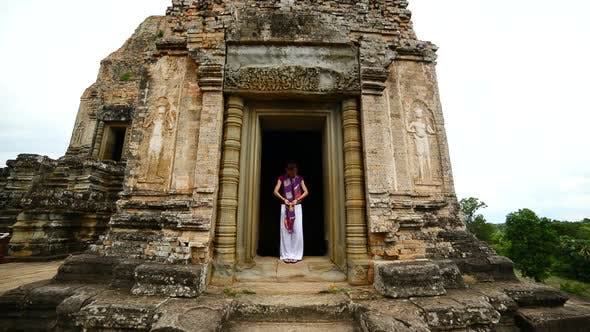 Female Buddhist Praying With Incense In Temple Doorway