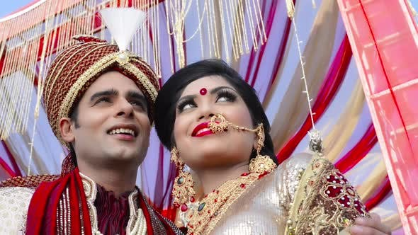 7807cbbdd6 Pan Shot Of Indian Bride And Groom In Traditional Wedding Dress Posing  Under A Mandap 3 (Stock Footage)