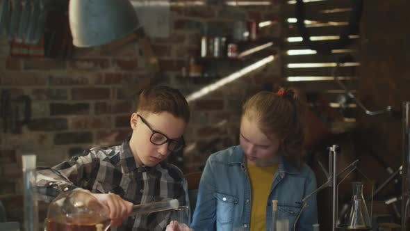 Young Boy and Girl Are Making Chemistry Experiments in a Garage at