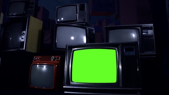 Retro TV Set turning On Green Screen among Many Vintage Televisions. Dolly.