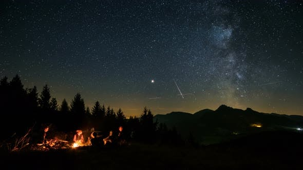 Friends Sitting over Campfire in Starry Night with Milky ...