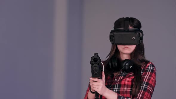 Girl Wearing Virtual Reality Glasses and Holding a Vr Gun by