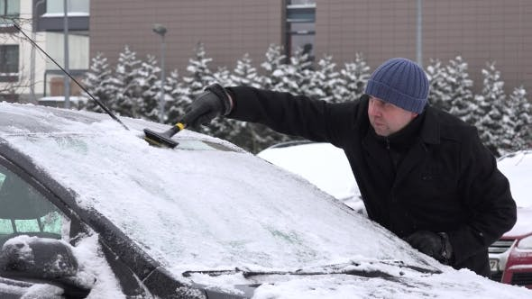 Man With Scraper Scraping Snow And Ice From Car Front Window