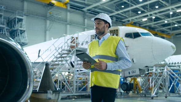 Aircraft Maintenance Mechanics Moving through Hangar Holding Tablet  Computer by Gorodenkoffs