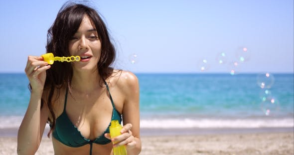 c951136a59 Pretty Young Woman Blowing Bubbles On a Beach by Daniel_Dash | VideoHive