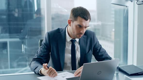 Successful Businessman Sitting At His Desk Working With