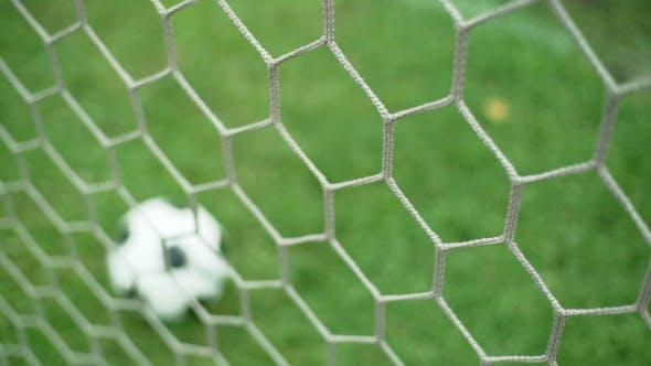 c76370b34 View of Soccer Ball Through Goal Net on Green Grass Field (Stock Footage)