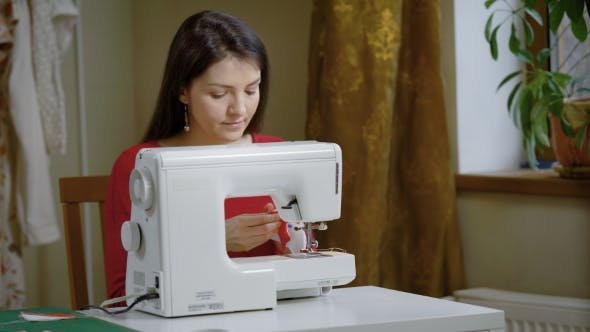 A Woman Works for a Sewing Machine in a Home Studio, a Lady Makes ...