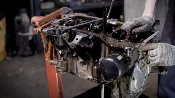 Motor Technician Is Disassembling Old Dirty Car Engine, Taking Out