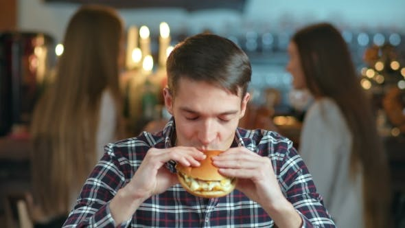 Unlimited Auto Sales >> Man in a Restaurant Eating a Hamburger and Smiling by ...