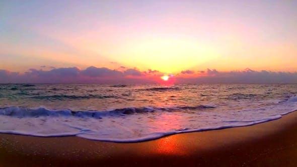 Ocean Waves Crashing on Sand Beach in Wonderful Orange Colored Warm