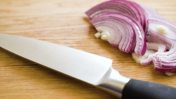 Sliced Onion And Knife On Wooden Cutting Board By