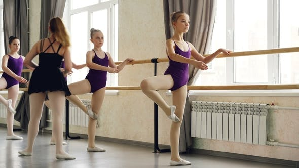 Serious Little Girls Learning Sequence of Ballet Positions