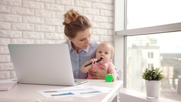 Working Mom with Child on Table. Businesswoman Holding Toddler ...