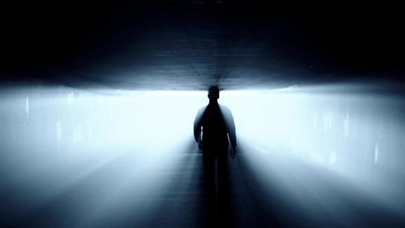 Silhouette of Person Walking in Tunnel To the Bright Blue ...