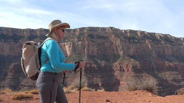 Fat Mature Woman With Trekking Poles And A Backpack Hiking