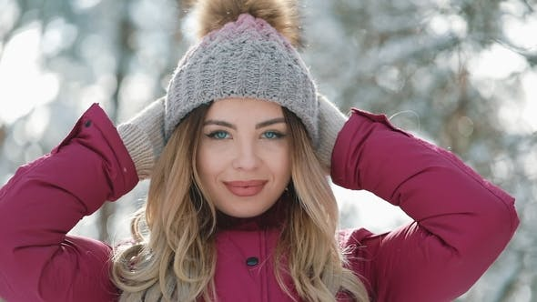 bdb0c2a90ed Pretty Woman in Winter Hat Smiles Standing Outside on the Snow in the  Forest. Portrait of a (Stock Footage)