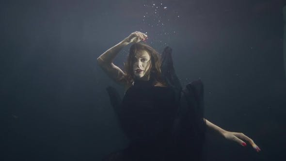 692cf187ee Young Woman in Black Dress Swimming Underwater on Dark Background (Stock  Footage)