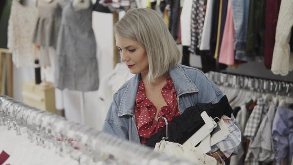 18fe05d8d06 Shopping Girl. Portrait of a Beautiful Woman in the Clothes Store. Young  Blonde Girl with Red Lips (Stock Footage)