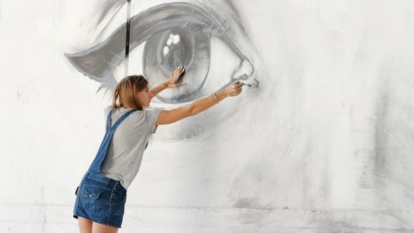 Graffiti Artist Drawing Face Of Woman And Eye With Paint On Street