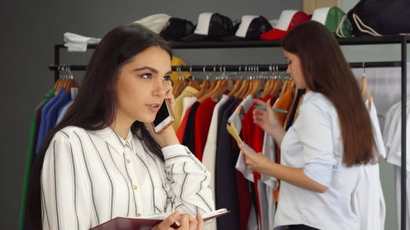 17d996106f Beautiful Female Shop Assistant Talking on the Phone, Working at the Clothing  Store (Stock Footage)