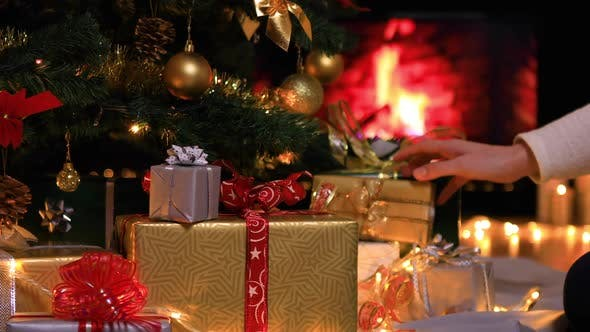 Woman Placing Gifts Under Christmas Tree Near Fireplace By Marianst