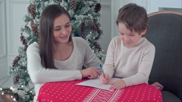 Happy Mother and Her Son Writing Letter To Santa by FancyStudio