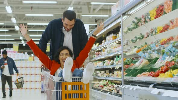 At The Supermarket Man Pushes Shopping Cart With Woman