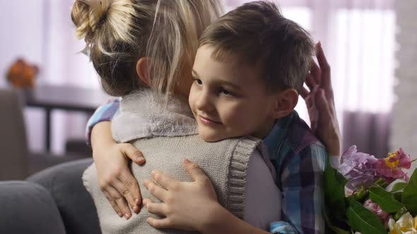 Closeup Cute Boy Felicitating and Hugging Mother