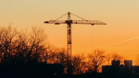 Tower Crane Working on Construction Site Orange Evening Sky