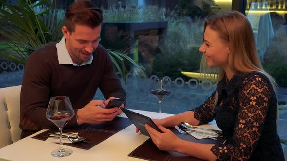 A Man and a Woman Sit at a Table in a Restaurant and Work on