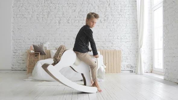 Child Boy Is Swinging On Rocking Horse