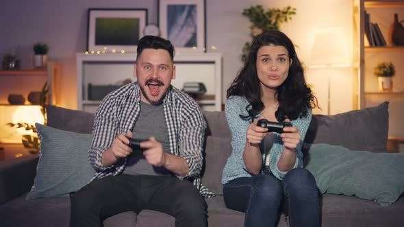 Cute Couple Husband And Wife Playing Video Games At Home Joyful Man Winning By Silverkblack