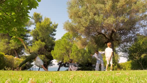 Family Doing Yoga and Relaxation Exercises Outdoors by SYNEL