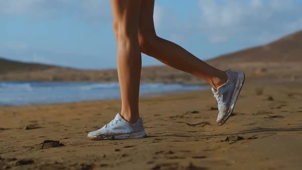 Close Up Shot Of A Woman In White Sneakers Walking On Beach