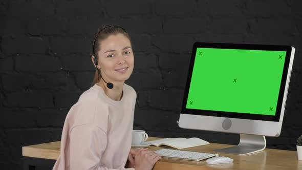 Smiling Woman Looking Into Camera with Headset and Computer