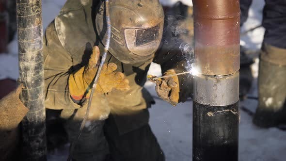 Worker Produces Pipe Welding on the Street  In Winter, at