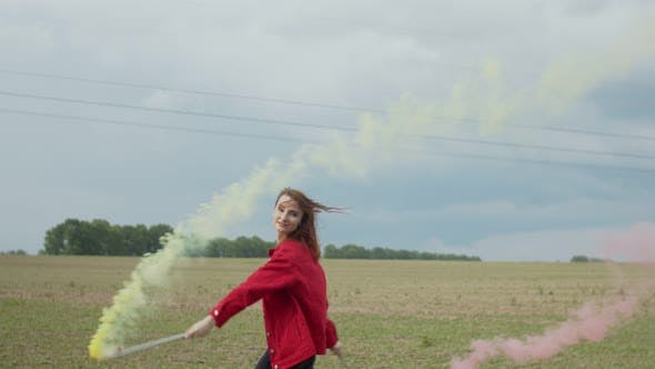 Woman with Colored Smoke Bomb Relaxing in Nature by Alona2018