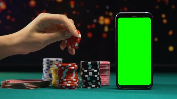 Casino Tokens And Cards Lying Near Green Screen Smartphone Online Gambling By Motortion