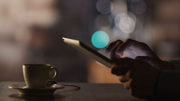 Man Using Tablet PC and Drinking Coffee in Cafe by