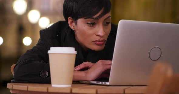 Casual young black woman checks social media while sitting alone at cafe by  Rocketclips