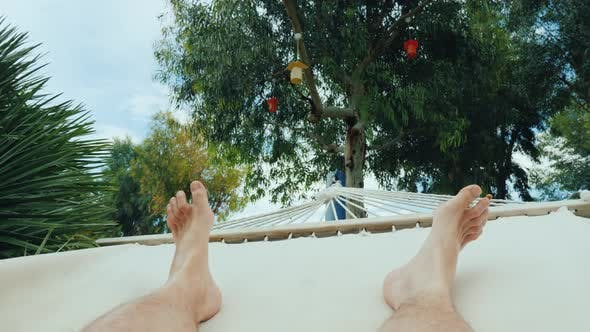 Men's Feet Swinging in a Hammock  One on Vacation Concept by