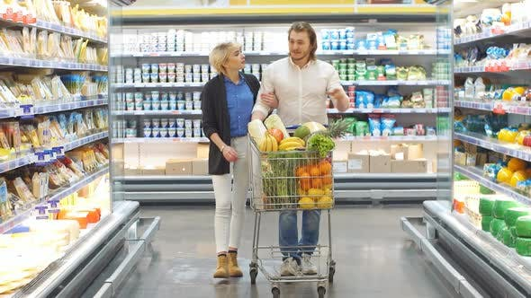 Couple In A Supermarket Shopping With A Shopping Cart Buying