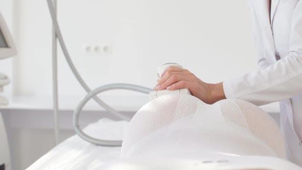 Female Doctor Hands Holding a Modern Medical Equipment for Body Skin