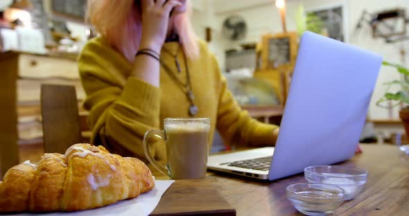 Young Woman Talking on The Phone While Using Laptop in Cafe