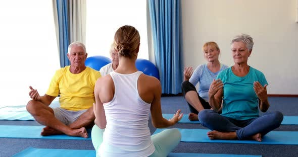 Trainer Assisting Senior Citizens In Practicing Yoga By Wavebreakmedia