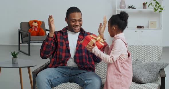 Cute Faro Kid Daughter Make Surprise Present for Dad Receive Gift Box Sit  on Sofa Black Man Father by jm_video