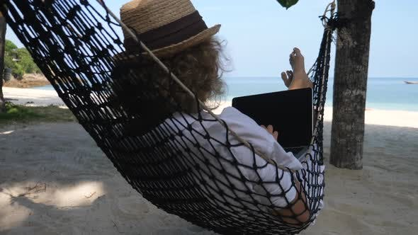 Businesswoman Working With Laptop Lying In Hammock On The